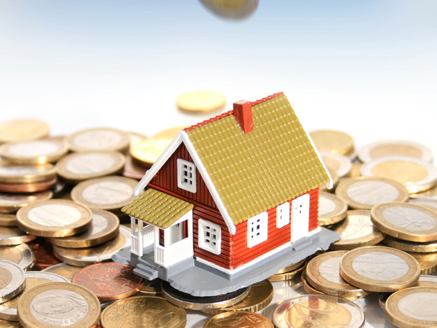 Invest in real estate concept. Hand and house on sky background.